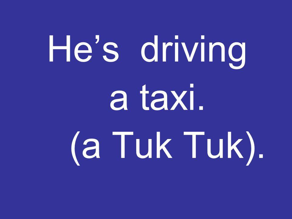 He's driving a taxi. (a Tuk Tuk).